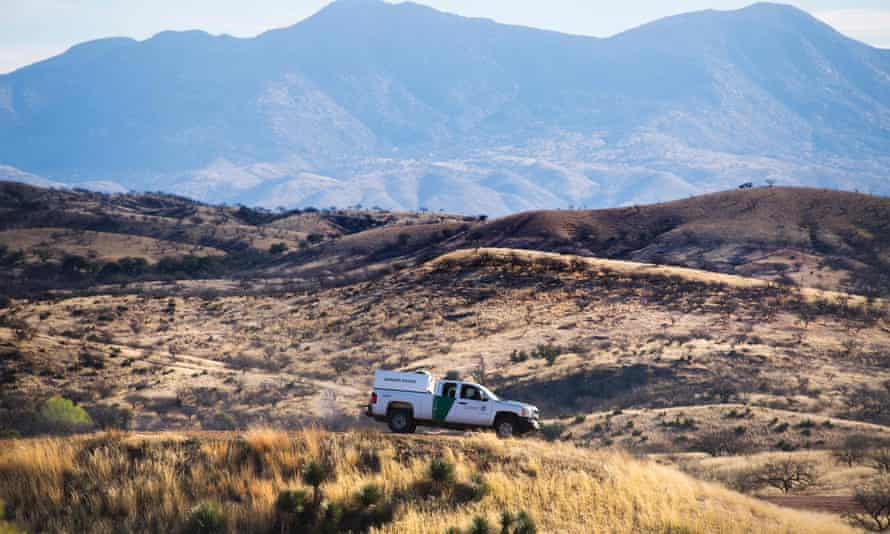 A Border Patrol agent parks on a hill top near the border fence in Nogales, Arizona. The Arizona-based No More Deaths group accused the Border Patrol of sabotaging water supplies.