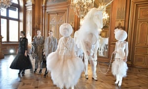 Models dressed in white leading a white 'unicorn' on the catwalk