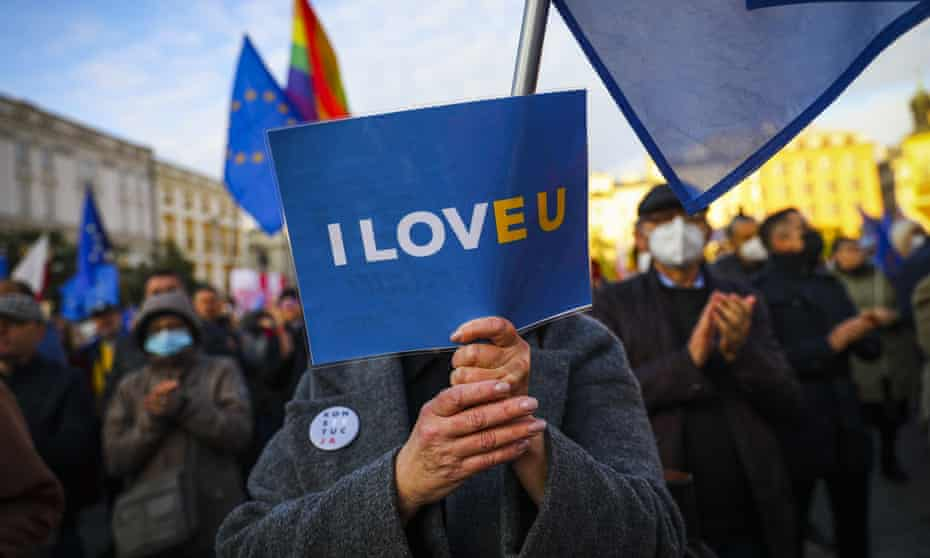 A woman holds an 'I Love EU' banner during a demonstration in Krakow, Poland on October 10, 2021