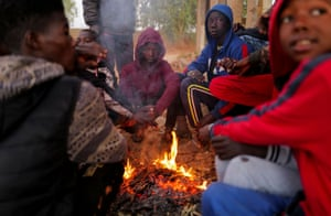Diop, 19, warms up with other jockeys and stable boys in front of a campfire before an early morning training session