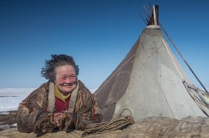 A reindeer herder women looks on at a nomad camp
