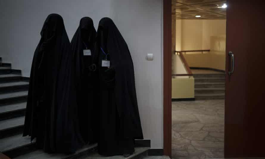 Women stand inside an auditorium at Kabul University
