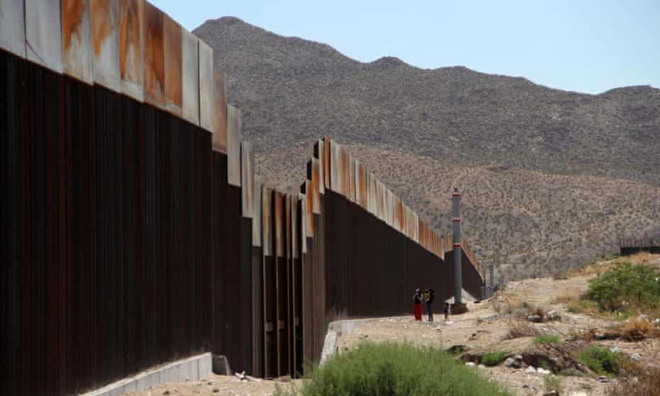 A family stands next to the border wall between Mexico and the United States, in Ciudad Juarez, Mexico on 23 May 2017.