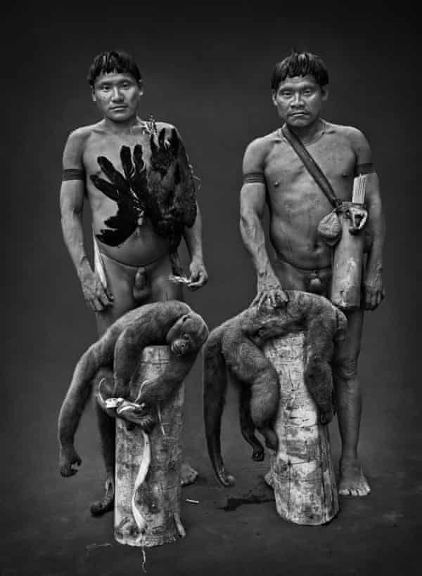 Hunters with a bird, a red-throated pipingguan, and two brown woolly monkeys brought down by poisoned arrows shot from blowguns.