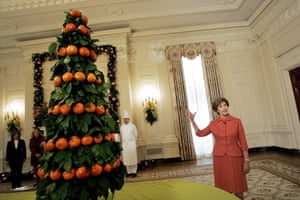 2005First lady Laura Bush talks and a centerpiece, made of fresh tangerines and lemons leaves in the East Room of the White House