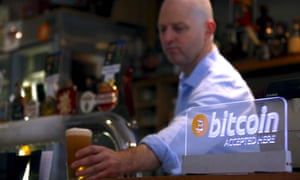 "publican places a beer on the counter of a pub in Sydney Australia next to a sign that says ""bitcoin accepted here"""