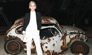 female model in front of wrecked old car