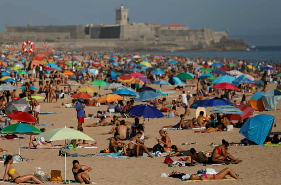 People enjoy the sunny weather at Carcavelos beach, near Lisbon, amid the coronavirus pandemic.