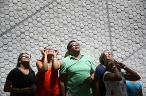 People in front of geometrical patterned wall watching eclipse.