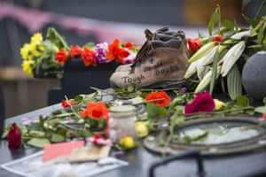 A pair of boots with the words 'Toughs as Old Boots' lie among floral tributes on Cox's houseboat