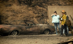 A resident surveys the scorched remains of her home and vehicle after the Saddleridge fire burned through Granada Hills.