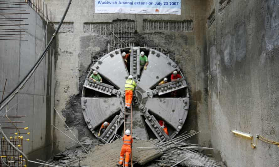 A 540-tonne boring machine breaks through the earth south of the Thames after completing a tunnel which now links the Docklands Light Railway to Woolwich as part of an ambitious expansion project.