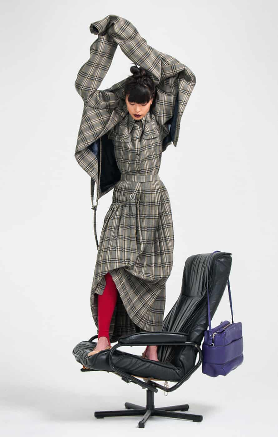 Model standing on a chair, wearing skirt suit by Joseph