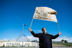 A protestor holding signage during the anti-Adani rally outside Parliament House in Canberra on 5 May.