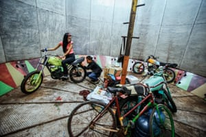 Purba and Palevi continue checking her bike, with other bikes in the foreground