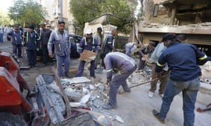 Syrian municipality workers clear debris from a building in the Mazze neighbourhood after the airstrike.