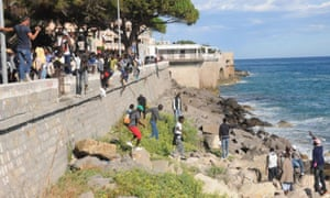 Migrants scrambling on rocks to evade border forces in Italy and enter France.
