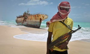 A Somali pirate pictured in 2012 in front of a Taiwanese fishing vessel that washed up after the crew were ransomed.