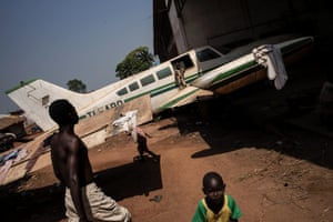 Children play near an abandoned plane at a refugee and displaced persons camp