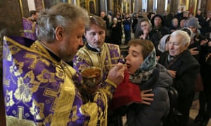 Russian Orthodox believers receive communion in Kazan Cathedral, St Petersburg