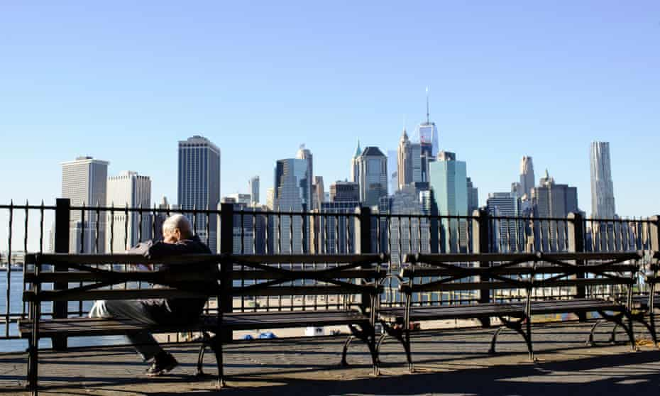 A man sits reading on a bench by the Brooklyn Heights waterfront