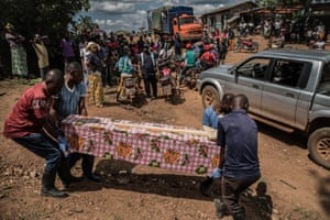 Motorcycle taxi drivers wait to transport mourners to the funeral of Angela Masika, 31, who died the day before in the town of Biakato in Eastern Democratic Republic of Congo's Ituri province. Test results had not yet revealed whether Ms. Masika died from Ebola