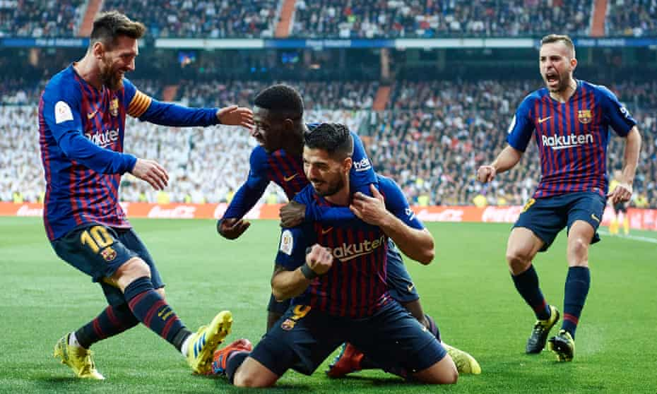 Luis Suárez is mobbed by his Barcelona teammates after after scoring his team's opener against Real Madrid.