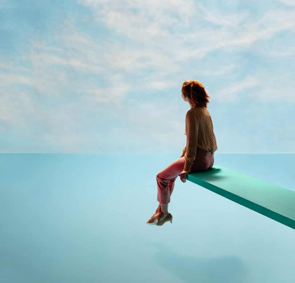 A model sitting on a diving board looking at the horizon