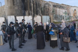 Palestinian women wait to cross the Qalandia checkpoint between the West Bank city of Ramallah and Jerusalem