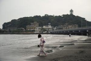 A woman wearing yukata strolls along the beach near Enoshima Island, Japan.