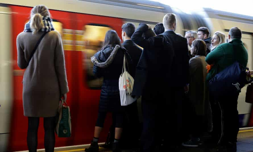 Commuters wait on the platform as a tube arrives on the London Underground, November 2016