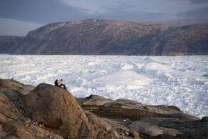 NYU student researchers sit on top of a rock overlooking the Helheim glacier.