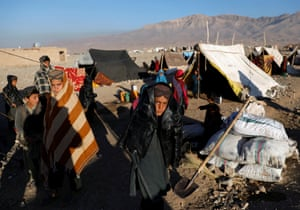 Children forced from their homes by drought stand outside a tent at a refugee camp in Herat province, Afghanistan