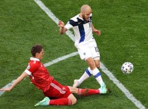 Finland's Teemu Pukki gets a shot away despite the attention of Igor Diveyev of Russia.