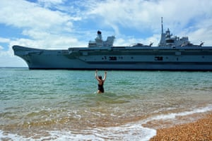 Portsmouth, UKSwimmer Dale Marie waves off the Royal Navy's aircraft carrier HMS Queen Elizabeth as it sailed through the mouth of Portsmouth Harbour, to set sail for sea trials
