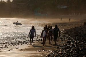 Surfers leave the water after the police ordered them to return to their hotels at El Tunco Beach as El Salvador's President ordered home quarantine for 30 days