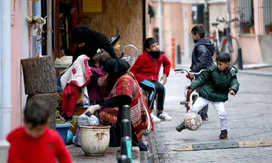 Syrian refugee children play as their mothers check free clothes baskets on the street of the historical neighborhood of Balat, Istanbul