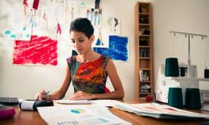 Hispanic dress maker uses calculator in studio