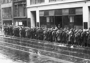 Unemployed men queue for handouts of bread in New York during the Great Depression.