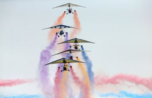 An aircraft team flies in formation with trails of smoke