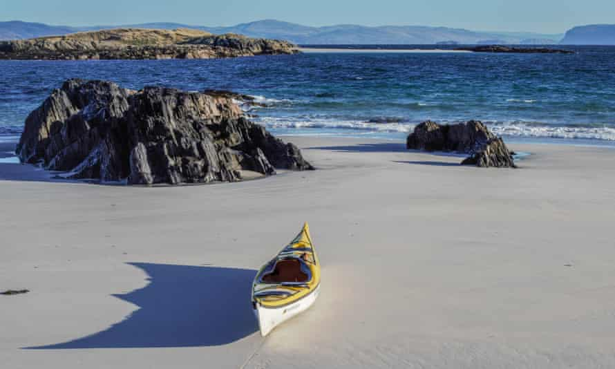 Empty sand beach with lone kayak