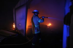 Horsley Park RFS Fire fighter Daniel Knox extinguishes a fire in a garage which was well alight when they arrived on a property near Potato Point. Photograph by Mike Bowers for Guardian Australia.