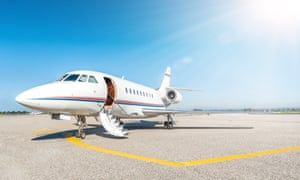 A private jet on the tarmac with a bright blue sky beyond
