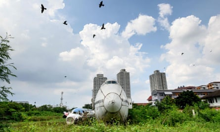 Birds fly over abandoned aircraft in the suburbs of Bangkok in October