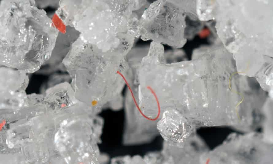 Tiny fragments and filaments of plastic inside and among table salt crystals.