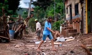 Elizangela da Silva crosses a damaged street in Sabara, in the metropolitan region of Belo Horizonte, Minas Gerais state, Brazil on Monday.