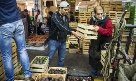 Workers lower crates of avocado for a customer at a market in Mexico City. Avocados regularly sell for more than 80 pesos per kilo – Mexico's daily minimum wage.