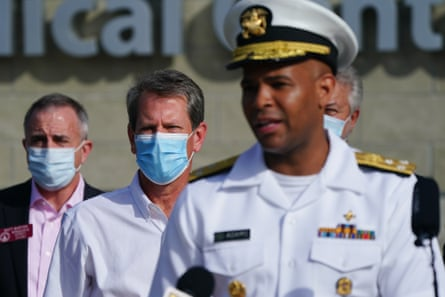 "Brian Kemp, governor of Georgia, center, listens while Vice Admiral Jerome Adams, U.S. Surgeon General, speaks during a 'Wear A Mask' tour stop in Dalton, Georgia, U.S., on Thursday, July 2, 2020. Governor Kemp on Wednesday expressed his skepticism about the need for a statewide mask mandate and his reluctance to impose one, calling it an issue he feels is ""overpoliticized."""