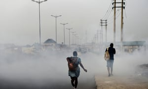 A schoolgirl walks past smoke emitted from a dump in the city of Port Harcourt, Nigeria.