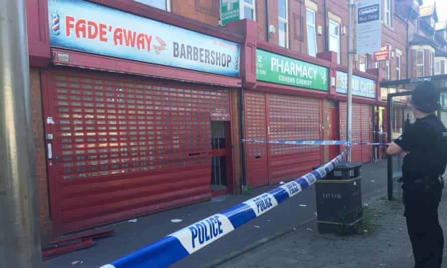 A police cordon outside the Fade Away barber shop in Princess Road in Moss Side.